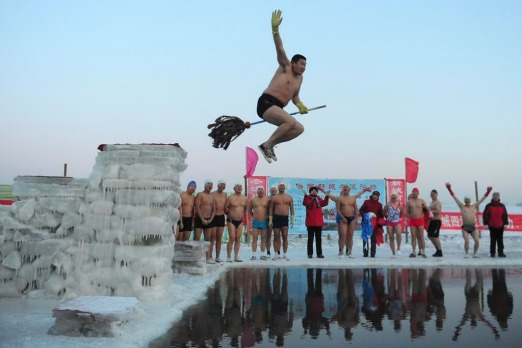 A winter swimmer jumps with a mop into the icy water of the Songhua River in Harbin, Heilongjiang province.