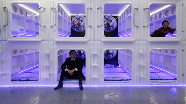 """Capsule bed"" manufacturer Eric Wong, left, and his son Osbert pose inside a modified capsule-like bedroom imported from ..."
