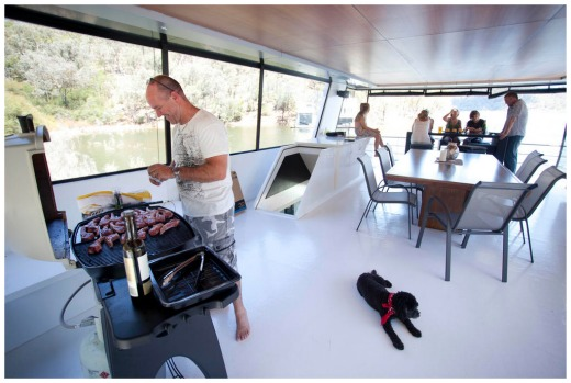 Noel Courtney upstairs on their lake eildon houeboat cooking a bbq lunch for everyone