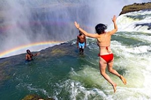 Woman jumping into Devil's Pool at Victoria Falls, Zambia, Africa