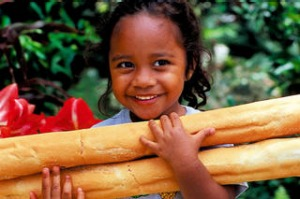 Young girl carrying fresh bread, Noumea, New Caledonia. Photograph by Travmedia. SHD TRAVEL MAY 25 FOOD sarahberry