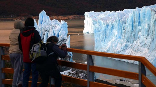 Tourists look at the Perito Moreno glacier after the rupture of a massive ice wall.