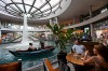 Customers of The Coffee Bean & Tea Leaf Singapore look on as a boat moves along an indoor waterway in Marina Bay Sands.