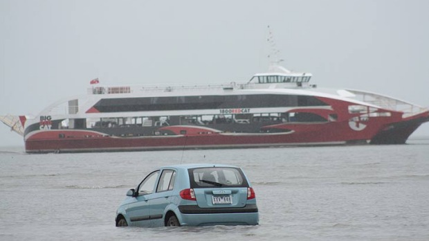 The Big Red Cat sails past the tourists' car. The low tide and a GPS navigation system lured them into the bay at Oyster ...
