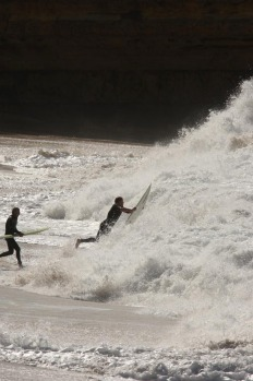 Local surfers confronting the shore break to paddle out at Bells Beach.