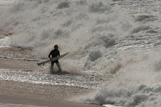 A surfer confronting the shore break to paddle out and catch some waves at Bells.
