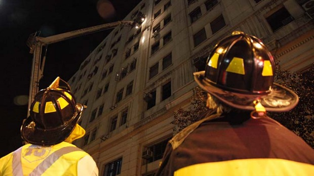 Firefighters inspect a building in downtown Santiago after the earthquake on Sunday.