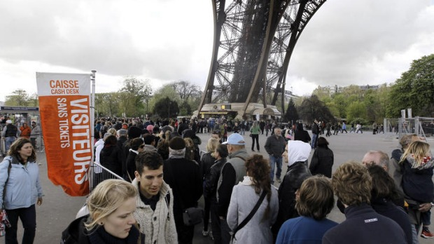 Visitors queue up in front of the Eiffel Tower.