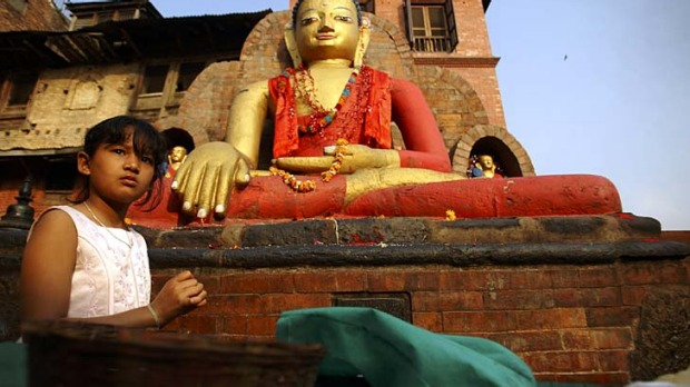 A girl sells goods in front of a Buddha statue at Swyambhu in Kathmandu.