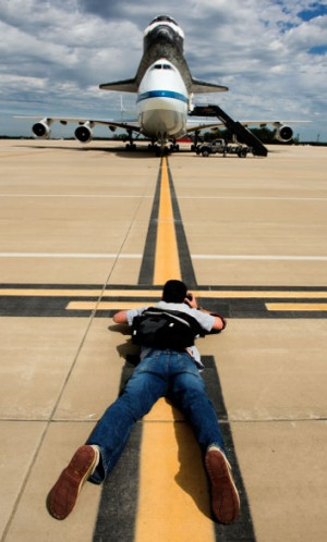 A photographer gets down low for a shot of the Space Shuttle Discovery after it's final landing on the back of a NASA's ...