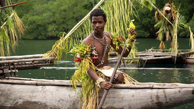 Flowing tribute ... paddling upriver in New Guinea.