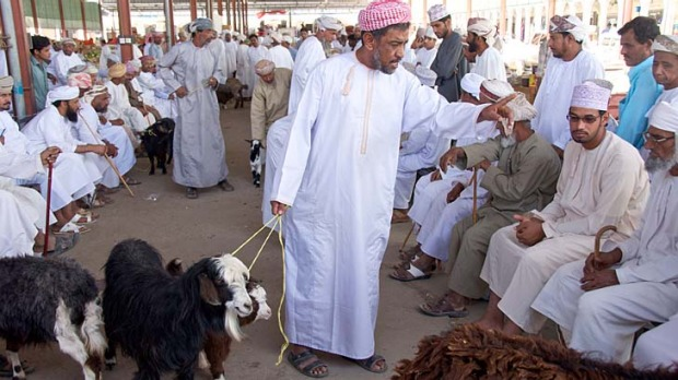An auctioneer haggles over the price of a goat in Ibra Souq.