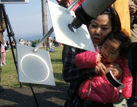A girl with her mother observe a solar eclipse, focused onto a white background through a telescope, at Takayama village ...