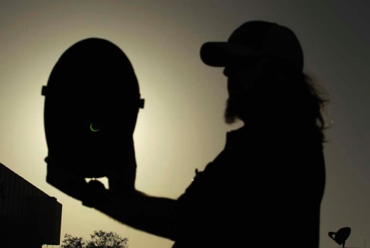 Dennis Vitt, 38, looks at an annular eclipse through a welding mask in Los Angeles, California.