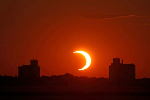The sun sets between the grain elevators in Abbyville, Kansas, during the annular eclipse.
