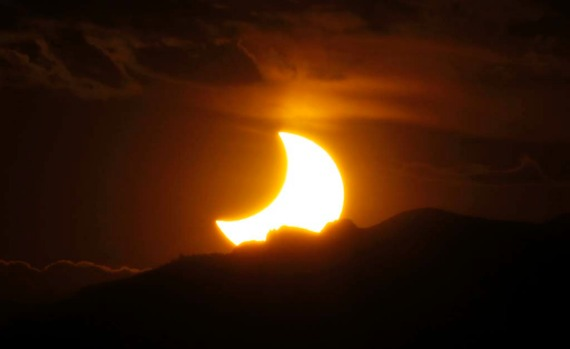 The annular solar eclipse is seen as the sun sets behind the Rocky Mountains from downtown Denver.