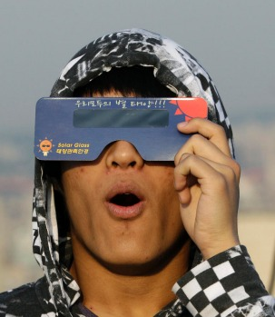 A South Korean astronomy student uses special sunglasses to observe an annular solar eclipse in Seoul, South Korea.