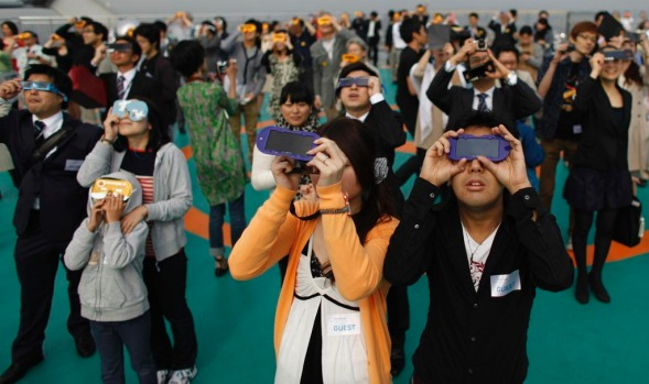 People watch an annual solar eclipse as seen at a rooftop of Roppongi Hills complex in Tokyo.