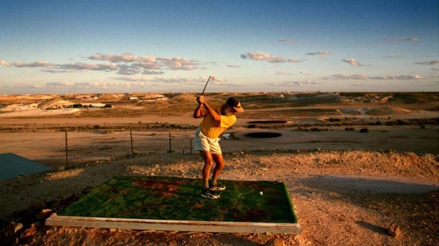 Teeing off at the driest golf course in the world in Coober Pedy.