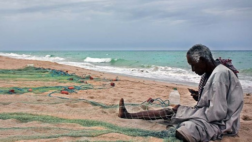 A fisherman tends his nets at Jebel Sifah on the Omani coast.
