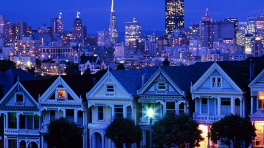 The city skyline rises over a row of Victorian houses.