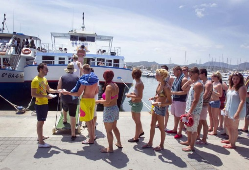 A worker collects tickets from tourists boarding a boat in Ibiza.