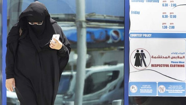 An Emirati woman passes by a dress code sign at a shopping mall in Dubai. An online campaign to get foreigns to dress ...
