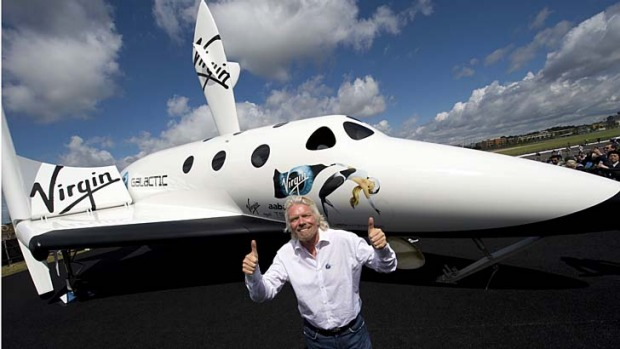 British billionaire Richard Branson poses in front of a model of Virgin Galactic's SpaceShipTwo at the Farnborough International Airshow. Branson hopes the first flight will happen next year.