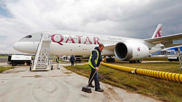A worker sweeps in front of the Qatar Airways Boeing 787 Dreamliner.