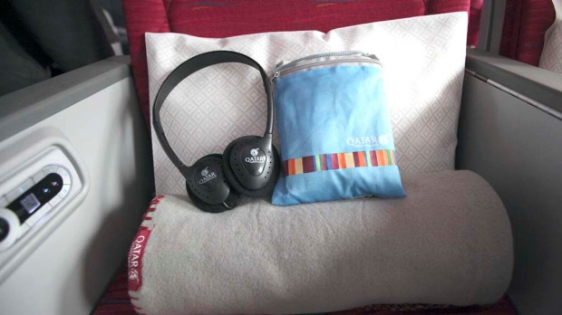 Headphones and amenities bag rest on board the Qatar Airways Boeing 787 Dreamliner.