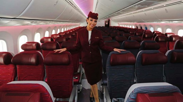 An air stewardess for Qatar Airways poses in the economy class cabin of the new Boeing 787 Dreamliner.