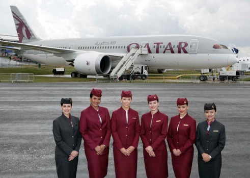 Qatar Airways flight attendants stand in front of the airline's new Boeing 787 Dreamliner at the Farnborough Air Show.
