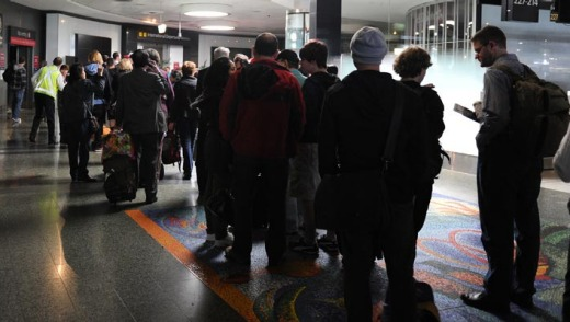 Passengers queue in darkness as workers scramble to restore power to Melbourne Airport.