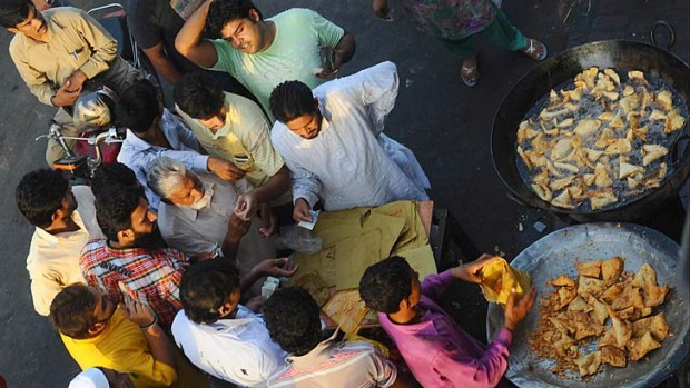 Soul food... Lahore workers buy samosas to break the first day of fasting during Ramadan.