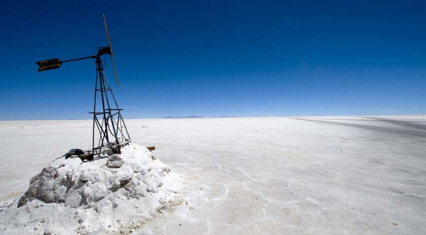 A tourist walks near the steam let off from fumaroles at the Uyuni salt flats, Bolivia.