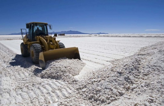 An excavator piles up salt at the Uyini Salt Flats in Bolivia.