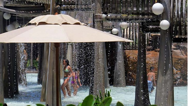 Water cascades onto visitors at the Menehune Bridge, a spray park at Disney's Aulani resort on Oahu, Hawaii.