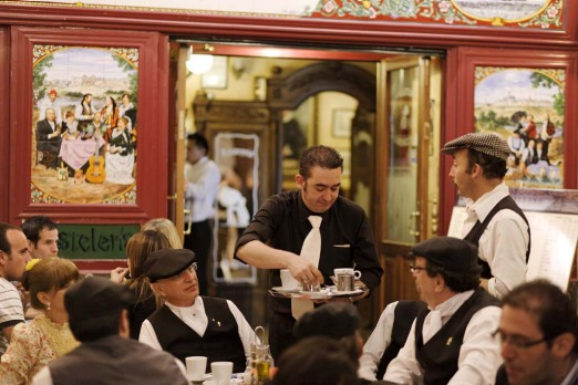 A waiter serving coffee in a pavement cafe at Fiestas de San Isidro Labrador, Madrid.