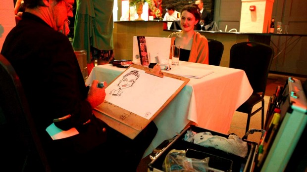Claudia Harley, from Melbourne, gets a caricature done at the dinner.