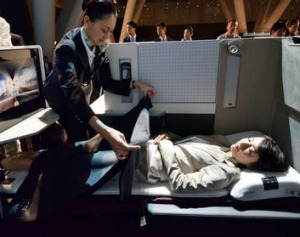 Japan Airlines (JAL) staff demonstrate the full flat seat for the business class of the company's international flights ...