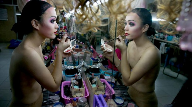 Pom, a ladyboy dancer at the Chiang Mai Cabaret show puts on her makeup backstage as up to 20 dancers get dressed before a performance.
