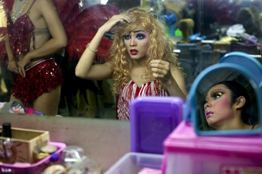 Pom, a ladyboy dancer at the Chiang Mai Cabaret show puts on a wig backstage as up to 20 dancers get dressed before a performance.
