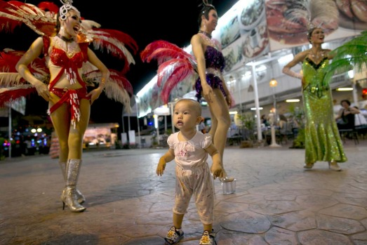 A toddler watches as ladyboys dance in the night market recruiting tourists to watch the show at the Chiang Mai Cabaret show.