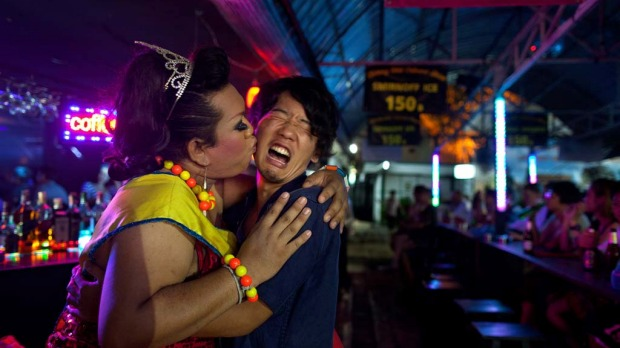 Lily throws a kiss on the cheek of a Japanese tourist as he reacts after the show at the Chiang Mai Cabaret.