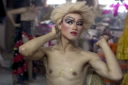 A ladyboy dancer puts on her wig getting into costume backstage at the Chiang Mai Cabaret show.