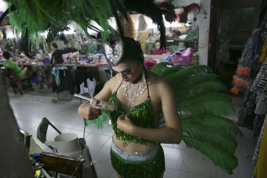 A ladyboy dancer takes a glue gun to her bra trying to quickly fix her costume backstage before a performance.