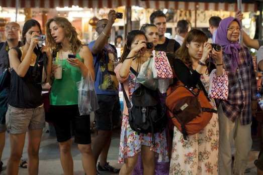 Tourists take photos of the Ladyboys dancing as they recruit customers at a night market for their nightly show.