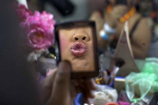 Lily, a ladyboy dancer puts on lipstick backstage as up to 20 dancers get dressed before a performance.
