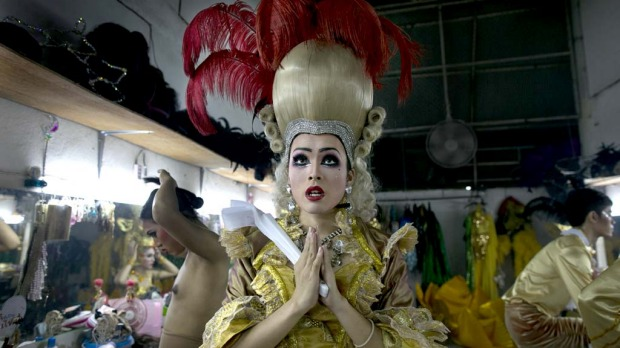 Pom, a ladyboy dancer at the Chiang Mai Cabaret does a quick Buddhist prayer for good luck before a performance.