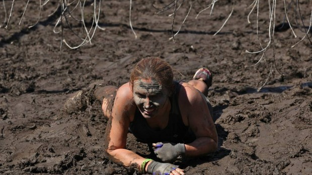 Competitor, Katie Doak crawls in mud to avoid cables of 11,000 volts in the Electroshock Therapy.